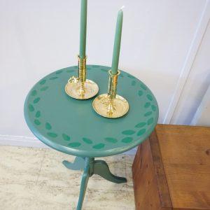 Handmålat grönt bord med mässingsljusstakar